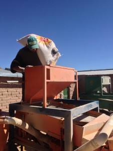 Loading Fair Trade  quinoa into the sorter and cleaning machine. APROCAY, Quillacas, Bolivia.  This quinoa will then be professionally cleaned and processed at the Jacha Inti plant in El Alto, 9 hours away.