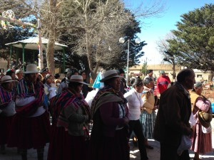 Women indigenous  leaders in red skirts with the Mallku in front parading at the  Salinas festival.